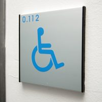 Informační štítek polepený modrým symbolem handicapované osoby a označením 0.112, přišroubovaný na strukturované bílé zdi