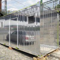 Kontejnerová stavební buňka polepená zrcadlovou folií, odraz automobilu, pražská náplavka s detailem Železničního mostu