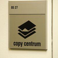 Informační kovový štítek s černým piktogramem a nápisem copy centrum, přišroubovaný na světlé zdi