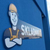 Postavička spokojeného skladníka doplněná nápisem SKLADNIK.CZ, modro-oranžovo-bílé, vše na jasně modré stěně, v pozadí auta a další budova modro-žluté fasády