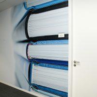 Laminovaná fototapeta s barevnou fotografií černých a modrých knih, bílé dveře s klikou, černá podlaha