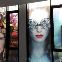 Potištěné folie s uměleckými fotografiemi modelek nalepené na skleněných příčkách s černými rámy
