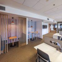 Potištěné fototapety s abstraktním motivem nalepené na zdi, open-space v kanceláři, dřevěné stolky s lavicemi a barovými židlemi za dřevěnou dekorační stěnou, kancelářské stoly s židlemi