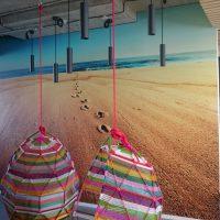 Matná fototapeta potištěná fotografií pláže a moře, nalepená na stěně, designová stropní svítidla, barevnéa moderní houpací křesla
