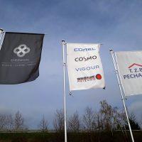 Tři vlajky obdélníkového tvaru připevněné zleva na šedých tyčích, levá vlajka černá s bílým logem a nápisy, prostřední bílá s různě barevnými logy, pravá světle šedá s modro-červeným logem, v pozadí napravo kus kamionu, jinak krajina a obloha