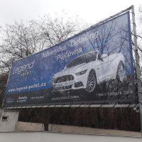 Exteriér, na kovové konstrukci napnutý modrý banner s motivem bílého auta, bílé nápisy, v pozadí opadané stromy