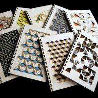 Devět knižních desek z překližky s různými vzory a kroužkovou černou vazbou na černém podkladu