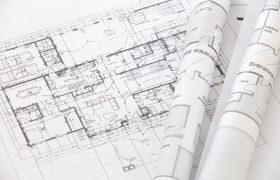 Projektový plán budovy, nárys na bílém papíře rozložený na stole, dvě role položené stranou