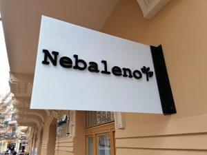 Nesvětelná reklamní výstrč Nebaleno na stěně budovy, černý 3D text, mléčné sklo, pískově žlutá fasáda