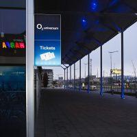 Prostředí chodníku u budovy, vlevo na budově připevněná modrá reklamní výstrč s bílým nápisem O2 universum a piktogramem i nápisem Tickets, v pozadí podpěrné sloupy a ulice