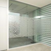 Samolepicí pískovaná folie s vyřezávanými motivy bitových postaviček z počítačových her, nalepená na skleněné příčce, vedle dvoje bílé dveře