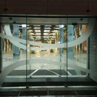 Skleněné dveře s automatickým otevíráním, polepené pískovanou folií ve tvaru vlnovek za nimi prosvětlený interiér budovy