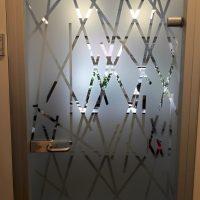 Samolepicí pískovaná folie s řezanými přímkami, nalepená na skleněných dveřích s dřevěným rámem