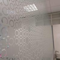 Samolepicí pískovaná folie s řezanými motivy kruhů a dalšími tvary, nalepená na skleněné příčce, pohled z levého boku