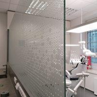Samolepicí folie s řezanými motivy kruhů a dalšími tvary, nalepená na skleněné příčce vedle zubařeského křesla
