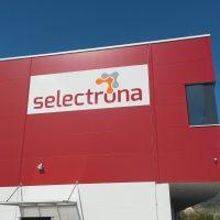 Logo selectrona na bílé desce připevněné nýtováním na červené fasádě krychlové budovy, v pozadí strom, obloha