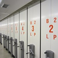 Červená písmena a číslice vyřezané z lepicí folie na řadě bílých desek jako značení, chodba