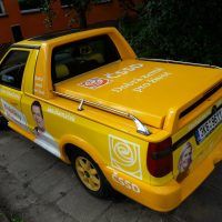 Shora vyfocený žlutý pick-up s bílými nápisy a různými postavami v rámci kampaně ČSSD, v exteriéru, na dlažbě, v pozadí budova a keř