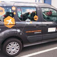 Z boku vyfocené tmavě šedé auto s oranžovo-šedo-černým polepem tvaru několika malých šestiúhelníků, oranžový a bílý nápis na zadních dveřích, logo na dveřích spolujezdce
