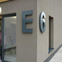 Roh domu s tmavě béžovou fasádou. Na levé straně velké šedé 3D písmeno E a na pravé straně rohu velká 3D číslice 6. Vlevo za písmenem balkonové dveře, vpravo za číslicí okno.
