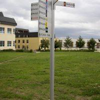 Šedý moderní rozcestník na trávníku, směrovky s barevným rozlišením pavilonů nemocnice