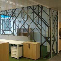 Skleněná rohová stěna uvnitř budovy polepená černými geometrickými motivy z folie, bílý a dřevěný kancelářský nábytek