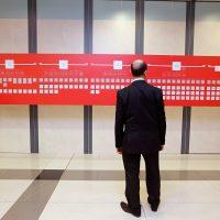 Muž v obleku, otočen zády k nám, stojí před potištěnou červenobílou obdélníkovou deskou instalovanou na závěsném systému