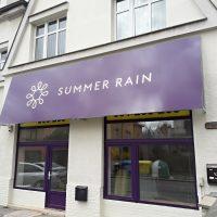 Velká dibond deska polepená fialovou folií s bílým logem SUMMER RAIN instalovaná nad výlohou provozovny, bílá budova s okny