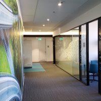 Chodba administrativní budovy, vlevo fototapeta na stěně, vpravo skleněné příčky polepené grafikou ze samolepicí pískované folie s geometrickými motivy