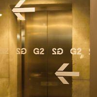 Dvě šipky doleva, mezi nimi řada nápisů G2, polep z pískové folie na skleněné příčce, v pozadí dveře výtahu