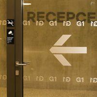 Opakovaný motiv G1 ve dvou řadách, mezi nimi šipka doleva, polep z pískované folie na skleněných dveřích, v pozadí chodba s nápisem RECEPCE na stěně