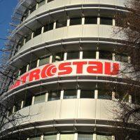 Červené logo Metrostav nalepené na oblém rohu budovy mezi okny, větve stromů