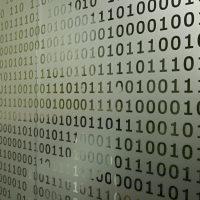 Samolepicí pískovaná folie nalepená na skle s vyřezávanými motivy jedniček a nul