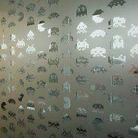 Samolepicí pískovaná folie nalepená na skle s vyřezávanými motivy bitových postaviček z počítačových her