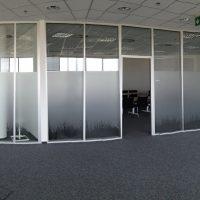 Stěna ze skleněných příček, spodní část tabulek polepená bílou pískovanou folií s řezaným dekoračním motivem, open-space v administrativní budově