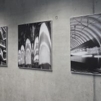 Šedá stěna s betonovým efektem, tři stříbrné čtvercové rámy s obrazy s černobílými fotkami