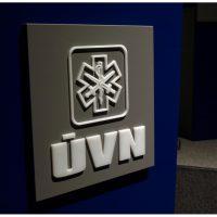 Bílý nápis a logo Ústřední vojenské nemocnice z opálového plexiskla, vyřezané laserem, umístěné na kovově/metalicky lakovaném plexi přilepeném na modré stěně v prostoru s šedými koberci.