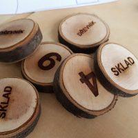 Šest menších dřevěných špalíků s vygravírovaným textem nebo číslem, na světle hnědém podkladu
