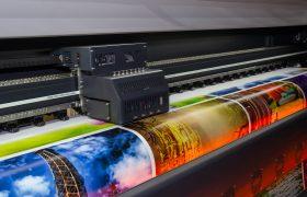 Hlava tiskového stroje v průběhu tisku barevných plakátů na lesklý papír