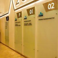 Skleněné světelné desky na zdi, svítící značení pater a nápisy, nad nimi světelná dekorativní lišta s číslicí 20