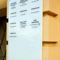 Informační panel z mléčného konexového skla, polepený samolepicí tiskovou folií s černým textem, přimontováno nerezovými distančními šrouby na zdi budově ordinace