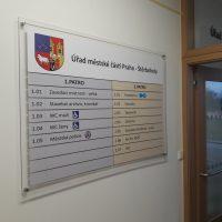Informační skleněný panel Úřadu městské části Praha-Štěrboholy, znak městské části, značení úřadu a místností, přimontováno na zdi chodby, pohled zleva, v pozadí dřevěné dveře