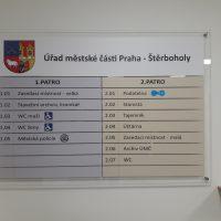 Skleněný informační panel Úřadu městské části Praha-Štěrboholy, znak městské části, značneí úřadu a místností, přimontováno na bílé zdi, pohled zepředu