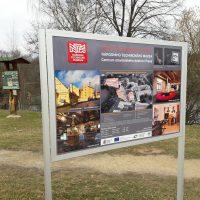 Hliníkový stojan s cedulí, pozvánka Centra stavitelského dědictví Plasy, fotky expozice, v pozadí přírodní informační totem