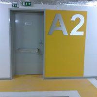 Stříbrné plastické označení A2 nalepené na žluté desce vedle šedých dveří