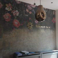 Laminovaná fototapeta s dekoračním motivem květin a odřeným efektem nalepená na zdi, zlaté 3D logo SUMMER RAIN, designová svítidla visící ze stropu