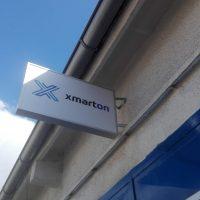 Bílá reklamní výstrč se světle modrým logem a tmavším nápisem xmarton, umístěná na fasádě budovy těsně pod okap, v pozadí modrá obloha, v popředí navazující modrá fasáda