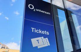 Světelná reklamní výstrč O2 Universum, modré pozadí, bílé logo, nápis a piktogram Tickets