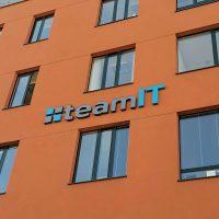 Detail oranžová budovy s černě lemovanými okny, uprostřed 3D šedo-modré logo a nápis team IT