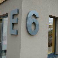 Šedé plastické světelné písmeno E a číslo 6 na rohu šedé fasády budovy, prosklené dveře a okno, nástěnné venkovní světlo